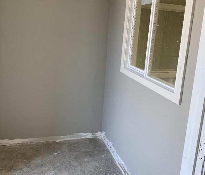 Office room with office window, taupe walls with floor ruined from water damage